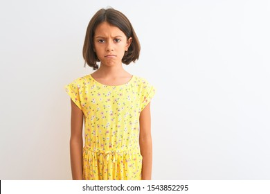 Young beautiful child girl wearing yellow floral dress standing over isolated white background skeptic and nervous, frowning upset because of problem. Negative person.