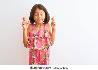 Young beautiful child girl wearing pink floral dress standing over isolated white background gesturing finger crossed smiling with hope and eyes closed. Luck and superstitious concept.