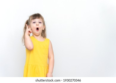 Young beautiful child girl wearing yellow dress standing over grey background with surprise face pointing finger to up, idea concept