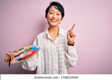 Young beautiful chinese artist woman painting using paintbrush and palette with colors surprised with an idea or question pointing finger with happy face, number one