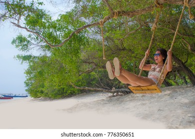 young beautiful Chinese Asian girl having fun on beach tree swing enjoying happy feeling free in Summer holiday tropical trip and travel concept