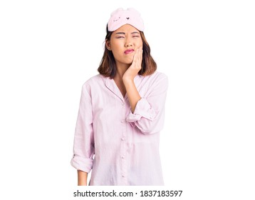Young beautiful chinese girl wearing sleep mask and pajama touching mouth with hand with painful expression because of toothache or dental illness on teeth. dentist