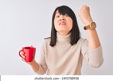 Young beautiful Chinese woman drinking red cup of coffee over isolated white background annoyed and frustrated shouting with anger, crazy and yelling with raised hand, anger concept
