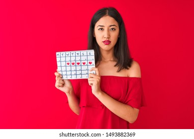 Young beautiful chinese woman holding period calendar standing over isolated red background with a confident expression on smart face thinking serious