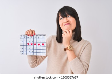 Young beautiful Chinese woman holding menstruation calendar over isolated white background serious face thinking about question, very confused idea