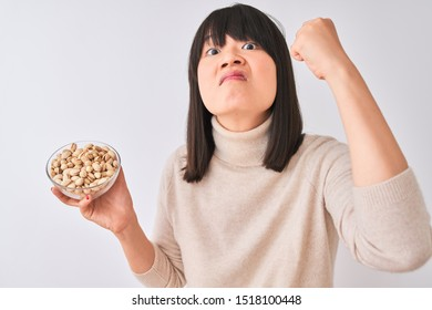 Young beautiful Chinese woman holding bowl with pistachios over isolated white background annoyed and frustrated shouting with anger, crazy and yelling with raised hand, anger concept