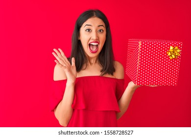 Young beautiful chinese woman holding birthday gift standing over isolated red background very happy and excited, winner expression celebrating victory screaming with big smile and raised hands