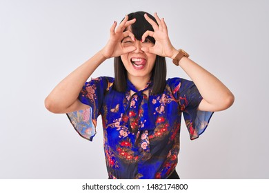 Young beautiful chinese woman wearing summer floral t-shirt over isolated white background doing ok gesture like binoculars sticking tongue out, eyes looking through fingers. Crazy expression.