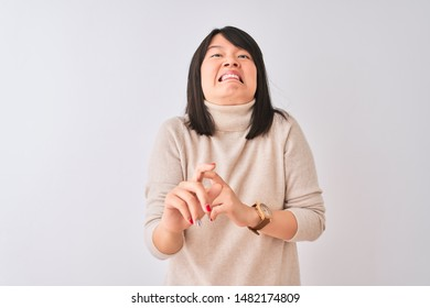 Young beautiful chinese woman wearing turtleneck sweater over isolated white background disgusted expression, displeased and fearful doing disgust face because aversion reaction. With hands raised.