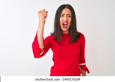 Young beautiful chinese woman wearing red dress standing over isolated white background angry and mad raising fist frustrated and furious while shouting with anger. Rage and aggressive concept.