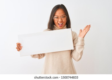 Young beautiful chinese woman wearing glasses holding banner over isolated white background very happy and excited, winner expression celebrating victory screaming with big smile and raised hands