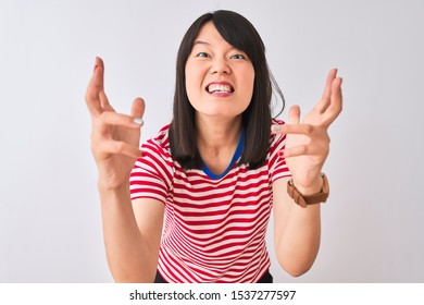 Young beautiful chinese woman wearing red striped t-shirt over isolated white background Shouting frustrated with rage, hands trying to strangle, yelling mad