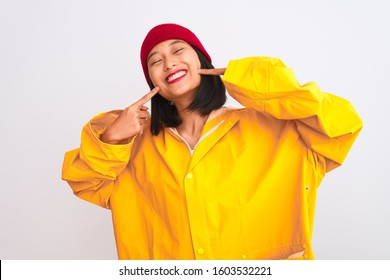 Young beautiful chinese woman wearing raincoat and wool cap over isolated white background smiling cheerful showing and pointing with fingers teeth and mouth. Dental health concept.