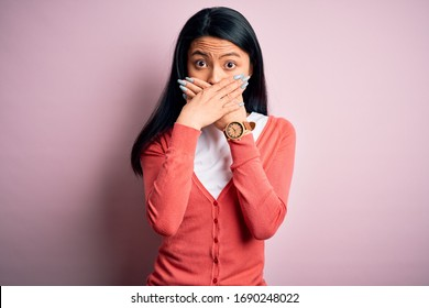 Young beautiful chinese woman wearing casual sweater over isolated pink background shocked covering mouth with hands for mistake. Secret concept.