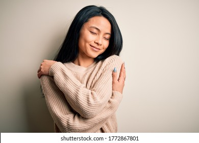 Young beautiful chinese woman wearing casual sweater over isolated white background Hugging oneself happy and positive, smiling confident. Self love and self care - Shutterstock ID 1772867801