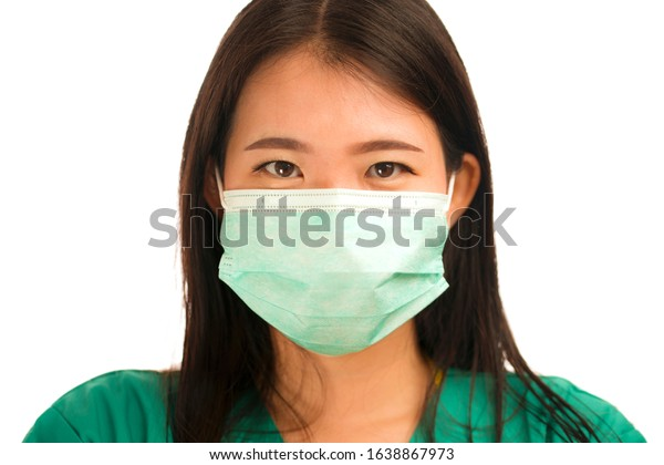 young beautiful and confident Asian Chinese medicine doctor woman or hospital nurse in green scrubs and surgical protective face mask in protection against virus outbreak concept