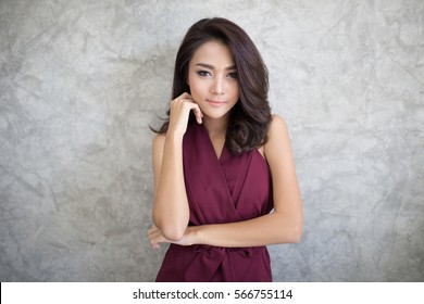 Young beautiful confident asian woman posing against a gray wall