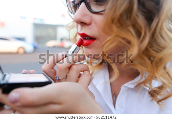 Young beautiful confident woman holds in hands compact powder, looking in mirror and paints lips red lipstick on street. Girl with curly hair and in glasses dressed in white blouse. Concept of make up
