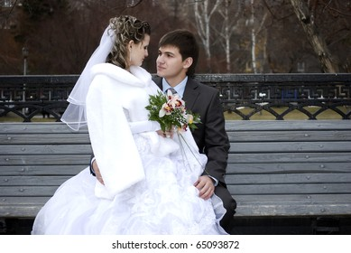 Young beautiful couple bride and groom sitting together on the bench on their wedding