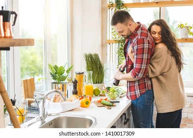 Young beautiful couple cooking together in their kitchen at home.