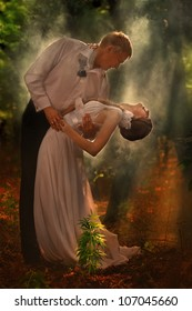 A young beautiful couple dance in a forest