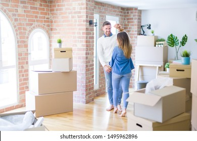 Young beautiful couple dancing  at new home around cardboard boxes