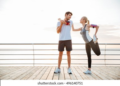 Young beautiful couple doing sports exercises at the beach pier