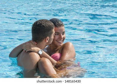 Young beautiful couple enjoying in pool on hot summer day