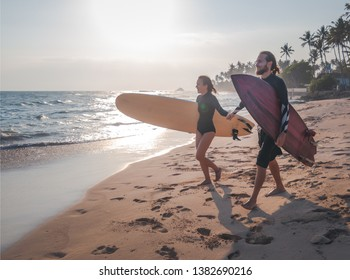 Young beautiful couple of friends on the ocean with surfboards in their hands, sports, active lifestyle, vacation, honeymoon
