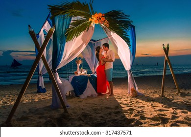 Young beautiful couple have a romantic dinner at sunset on a tropical beach . Honeymoon.