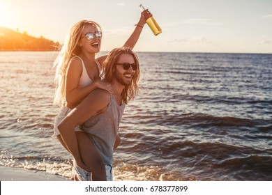 Young beautiful couple is having fun on beach, drinking beach and smiling.
