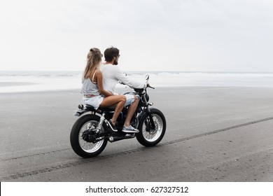 Young beautiful couple hipsters riding retro motorcycle on the beach, outdoor portrait, posing, in jeans shorts and t-shirts, bearded guy, blonde girl, travel together, ocean, sea