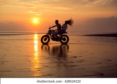 young beautiful couple hipsters in stylish clothing for a retro motorcycle on the street, outdoor portrait,posing in jeans and t-shirts,bearded guy,blonde girl,travel together go on the water splashes