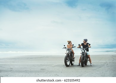 young beautiful couple hipsters in stylish clothing for a retro motorcycle on the street, outdoor portrait,posing in jeans and t-shirts,bearded guy,blonde girl,travel together