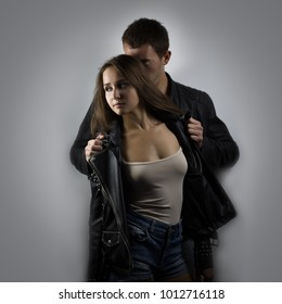 Young beautiful couple hugging in studio. Shallow depth of field