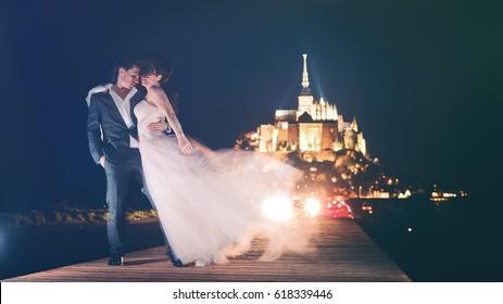 A young beautiful couple just married, on their honeymoon, is posing at night for their wedding pictures, at the charming and romantic location of Mont Saint Michel (France)