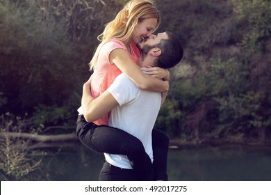 Young beautiful couple kissing in nature
