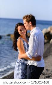 Young beautiful couple kissing on sea background.