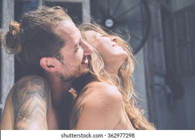 Young beautiful couple kissing . Tanned woman and a man with a tattoo .