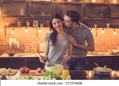 Young beautiful couple in kitchen. Family of two preparing food. Man kissing woman while making delicious fresh salad. Nice loft interior with light bulbs