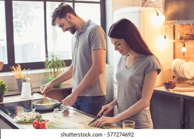 Young beautiful couple in kitchen. Family of two preparing food. Couple making delicious pasta. Nice loft interior with light bulbs and big window