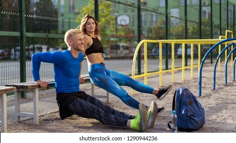 Young beautiful couple leaned their hands on the horizontal bar, doing exercises together. Girl looking at man