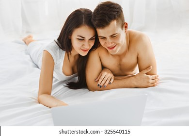 Young beautiful couple looking at laptop while lying on the bed in their bedroom. Communication technology