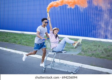 Young beautiful couple in love, boyfriend and girlfriend ride on shopping cart with orange smoke bomb, hipsters having fun in city mall