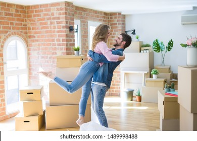 Young beautiful couple in love celebrating moving to a new home around cardboard boxes