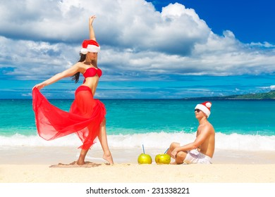 Young beautiful couple in love having fun in the waves dressed in red Santa Claus hats. Christmas on the tropical coast.