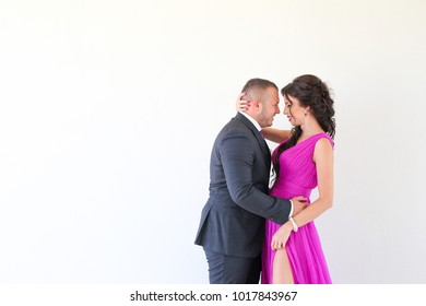 young beautiful couple in love. Man in suit and  pretty woman in a beautiful long purple dress on white background