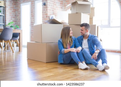 Young beautiful couple in love moving to new home, sitting on the floor very happy and cheerful for new apartment around cardboard boxes