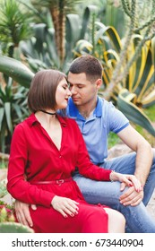 Young beautiful couple in love sitting near big cactuses in the park. Park Aivazovsky, Crimea.