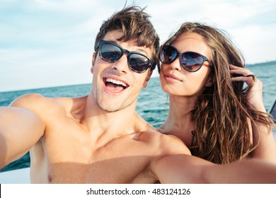 Young beautiful couple in love taking selfie on sailing boat